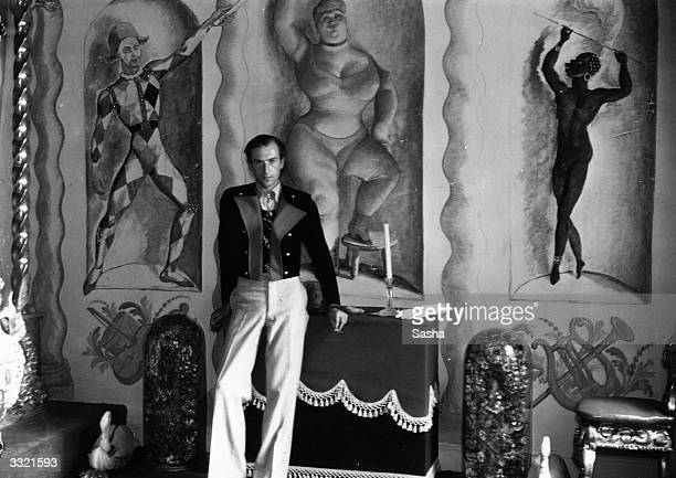 English photographer and designer Sir Cecil Beaton in the 'circus room' at his home 'Ashcombe' in Wiltshire. The murals were by Pavel Tchelitchew,...
