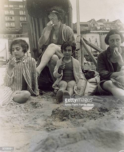 EXCLUSIVE Original Publication From left to right Margot Frank Mrs Schneider Anne Frank and Edith Frank eat ice cream on a beach at Zandvoort Holland...