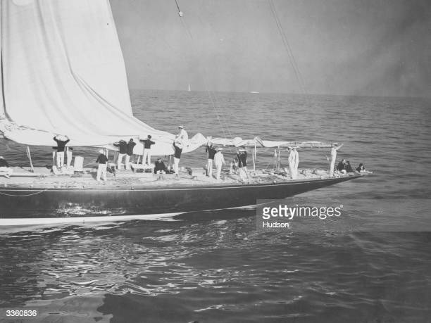 The crew of America's Cup yacht 'Endeavour' unfurling its mainsail The yacht's owner Thomas Sopwith is sitting at the stern with guests