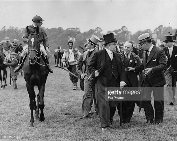 Prince Aly Khan chats with the jockey as his father the Aga Khan leads in 'Bahram' after winning the 1935 Derby at Epsom