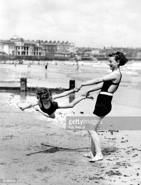 Woman swings a child on the beach at Bridlington, Humberside, during Whitsun holiday.