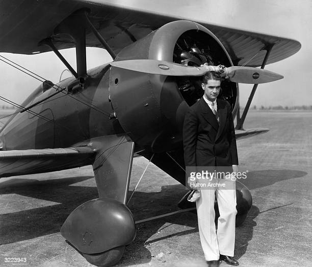Portrait of aviator and film producer Howard Hughes standing in front of his new U.S. Army Boeing pursuit airplane. The single-seater was rebuilt...