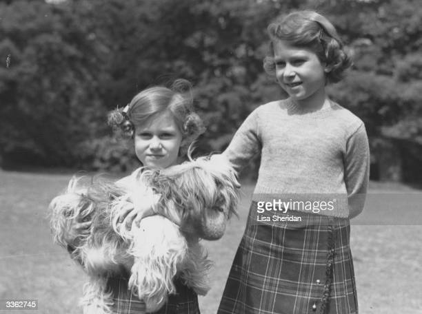 Queen Elizabeth II and her younger sister Princess Margaret in the grounds of the Royal Lodge Windsor Princess Margaret is holding one of their pet...