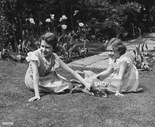 Queen Elizabeth II and her younger sister Princess Margaret sitting on the grass in the grounds of the Royal Lodge Windsor stroking a corgi