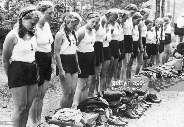 Young German women of the Hitler Youth Movement stand in line as they check their equipment at a vacation camp in the German Alps. They wear white...