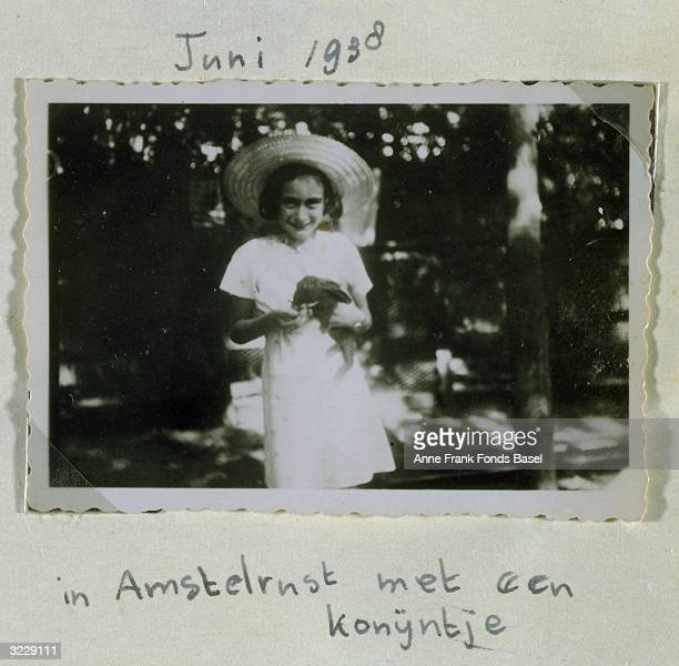 EXCLUSIVE Portrait of Anne Frank holding a rabbit and wearing a sun hat taken from her photo album Amsterdam Holland