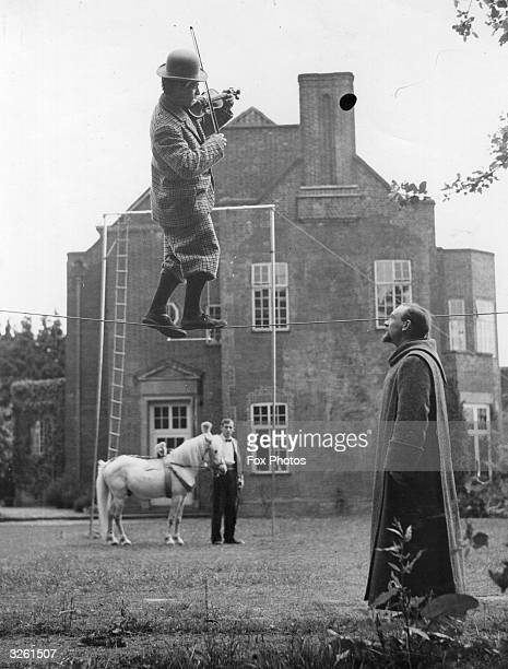 The Benedictine Brother Superior of Mount Olive Monastery Moon's Hill near Farnham watching a trainee tightrope walker rehearsing his comic act