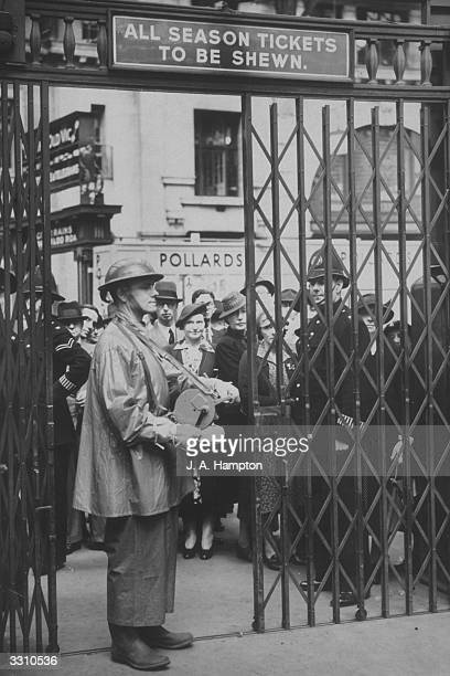 A railway ARP worker operating a handsiren at the entrance to a platform at Waterloo Station before the AirRaid Precaution Instructional train left...