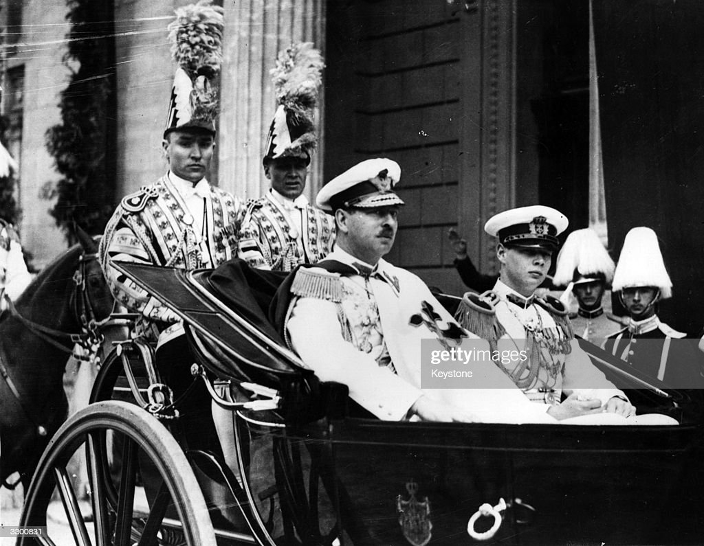 Carol II (1893 - 1953), king of Romania from 1930 to 1940, en route to open the new parliament in an open carriage with Crown Prince Michael, later King Michael of Romania.