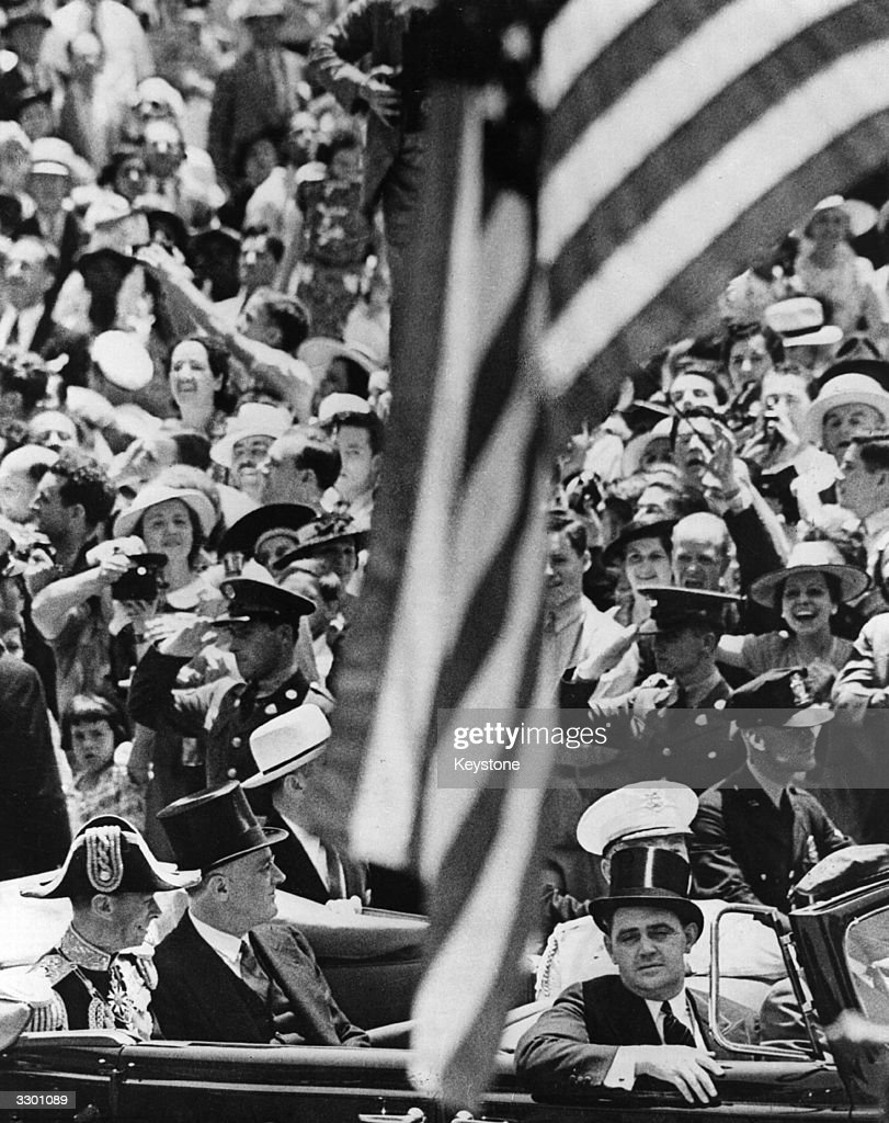 King George VI of Great Britain and President Franklin Delano Roosevelt (1882 - 1945) in an open-topped car on the procession from Union Station to the White House, with a packed crowd in the background.