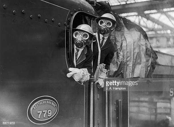 The driver and fireman of an ARP train wearing gas masks and helmets as they arrive at Waterloo Station, London.
