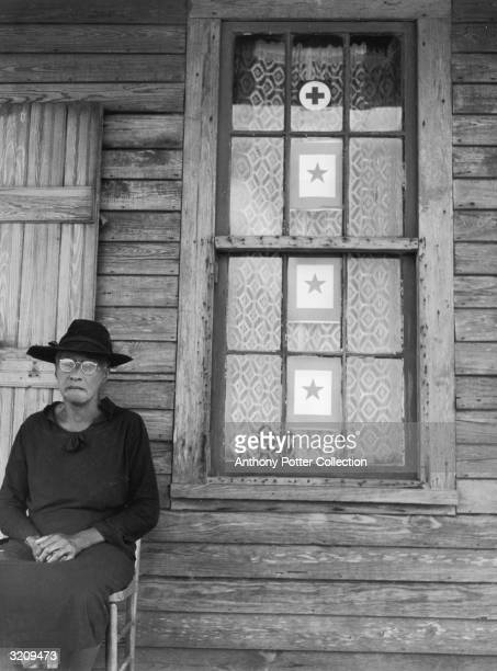 Mother of three soldiers wears all-black attire while sitting on her porch, Placquemines Parish, Louisiana, World War II. The front window displays...