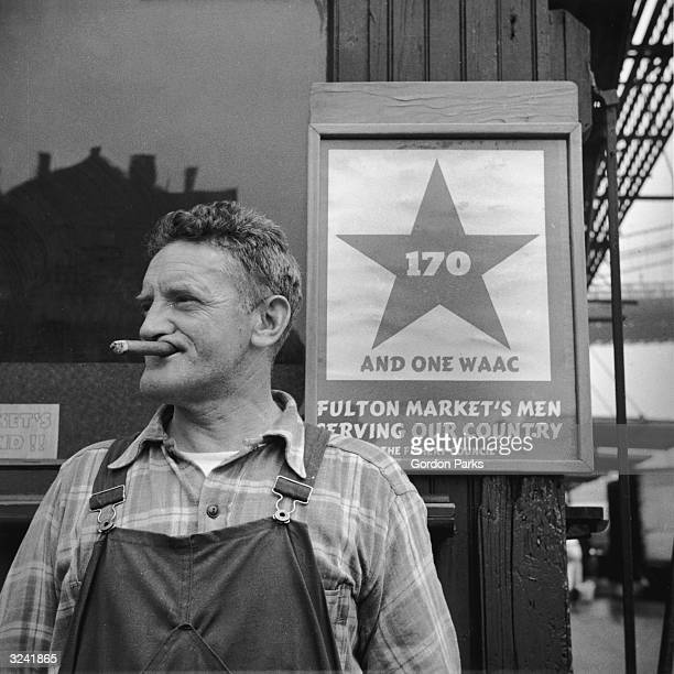 Man smokes a cigar while standing next to a World War II sign at the Fulton fish market, New York City. The sign reads: '170 and one WAAC. Fulton...