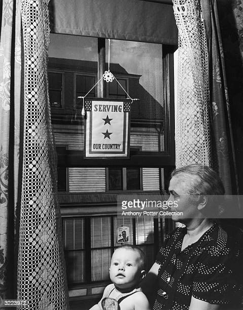 Mrs Joseph Lopez, mother of two soldiers, holds her baby granddaughter, Dorothy, in front of a window with a U.S. Flag and star sign in support of...