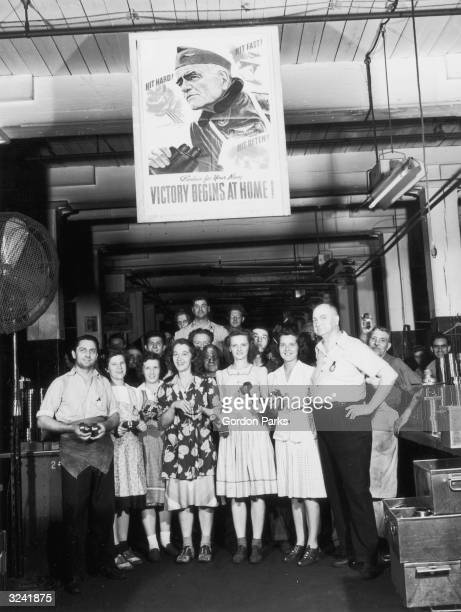 Portrait of workers gathered beneath a 'VICTORY BEGINS AT HOME' poster at a bearing factory, New Britain, Connecticut, World War II.