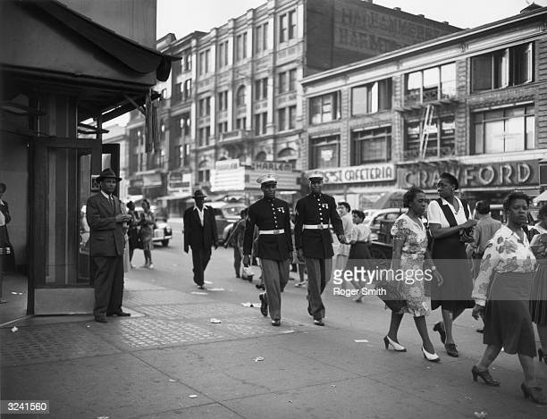 Two African-American Marines walk down a street in Harlem, New York City, World War II.