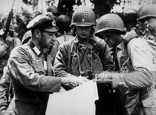 A German officer explains details of a military map captured with him to members of the Allied Expeditionary Force who made the initial landings in...