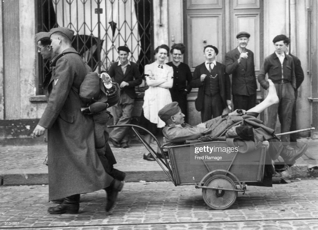 A wounded German officer captured during the liberation of Cherbourg is dragged along in a handcart, to the amusement of onlookers.
