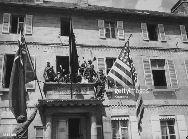 American soldiers hoisting the Stars and Stripes the Union Jack and the Tricolour on Cherbourg Town Hall after the town was liberated by the Allied...