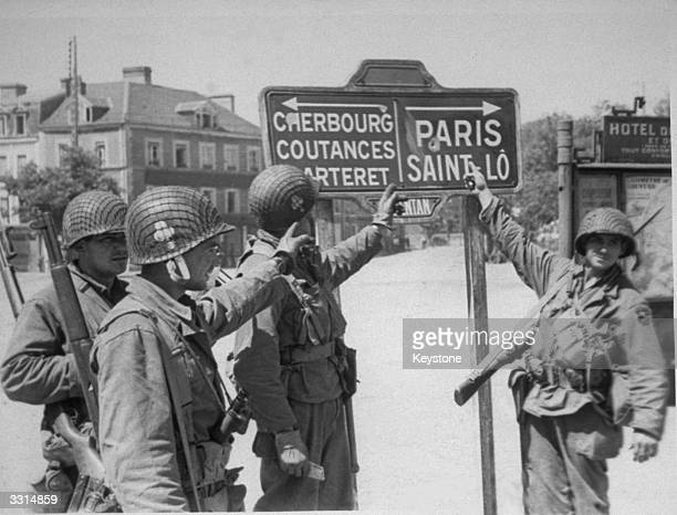 American troops pause to examine a bulletriddled sign pointing the way to Paris and Cherbourg as they move through the streets of Carentan after they...