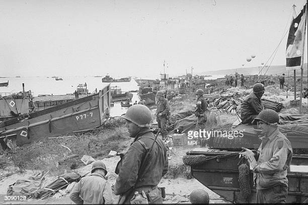 American troops stand by with stores on Omaha Beach after the Dday landings