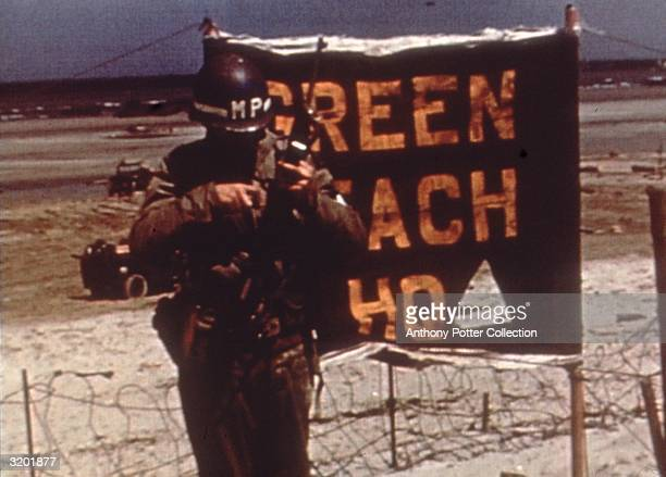An American military policeman checks his weapon in front of a barbed wire fence and a 'Green Beach Headquarters' sign during the Normandy Invasion,...