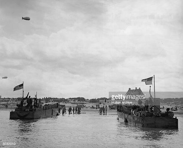 Fulllength view of US soldiers disembarking from one of two American landing craft on the Normandy beachhead during the Allied invasion of Normandy...