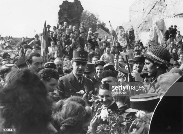 General Charles De Gaulle is offered flowers by the crowd surrounding him during celebrations to mark the Liberation of Paris from Nazi rule