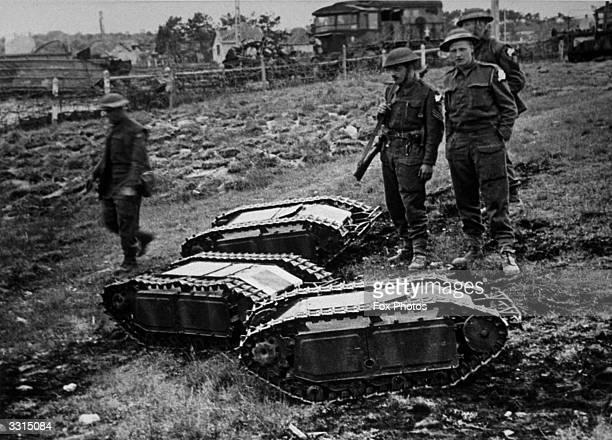 In France British soldiers inspect three German 'Doodlebugs' remote controlled tanks loaded with high explosives