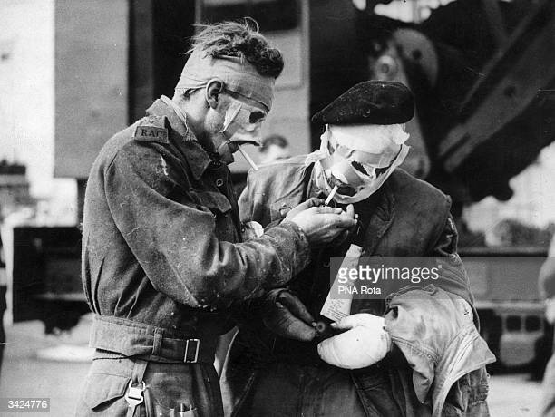 Sent home from Europe after receiving severe burns Lt PE Reeve lights a cigarette for Corporal Rodgers as they come ashore to Britain