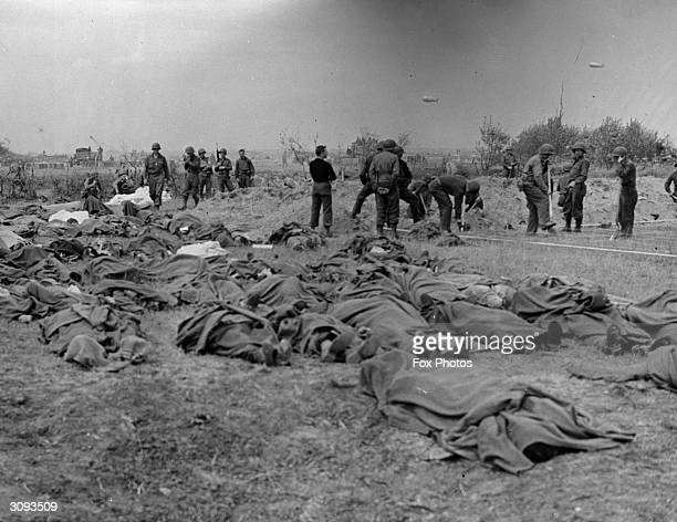 The bodies of American soldiers lie on the ground in Normandy, France, awaiting burial, following the D-Day Allied invasion.
