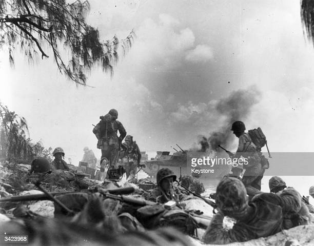 Marines dig in after landing on a beach on Saipan and prepare to attack the Japanese, who are defending the island. An American armed amphibious...