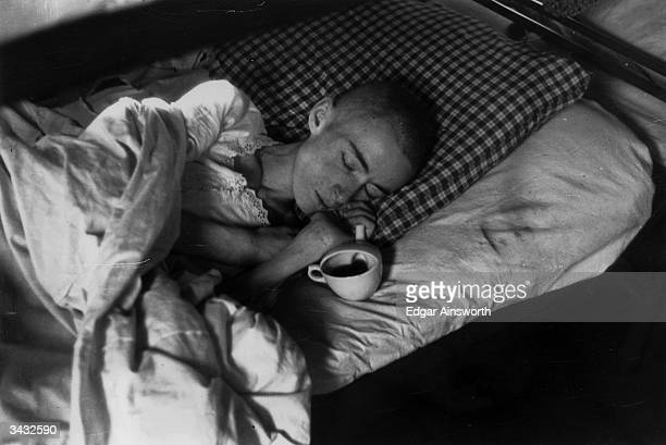 A woman prisoner from Belsen with shaven head lies asleep a feeding cup lies beside her balanced on the mattress Original Publication Picture Post...