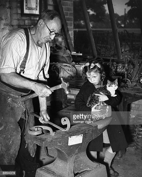A young girl watches as Mr Grantham hammers wrought iron on his anvil in Sussex