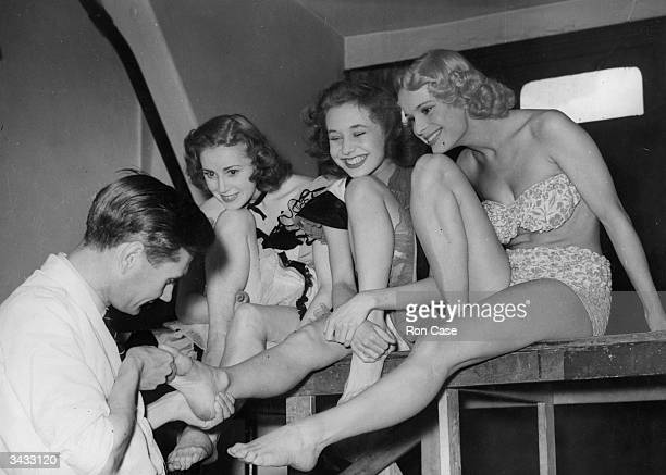 Dancers at the Windmill receiving pedicures from a chiropodist during National Foot Health Week Left to right Rae Berry Margot Holden and Linda Gray