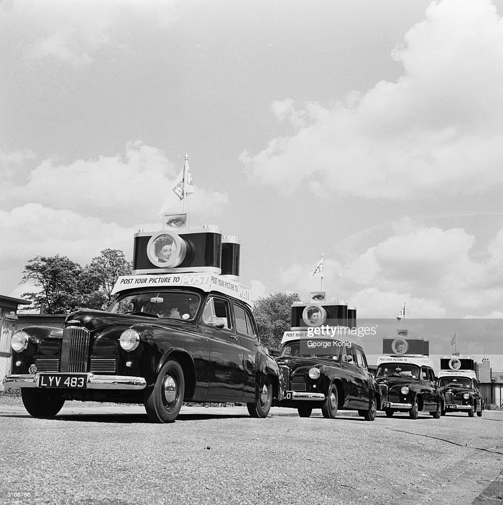 A procession of cars with large model cameras on their roofs, advertising a Picture Post photography competition with the slogan 'Post your pictures to Picture Post'.