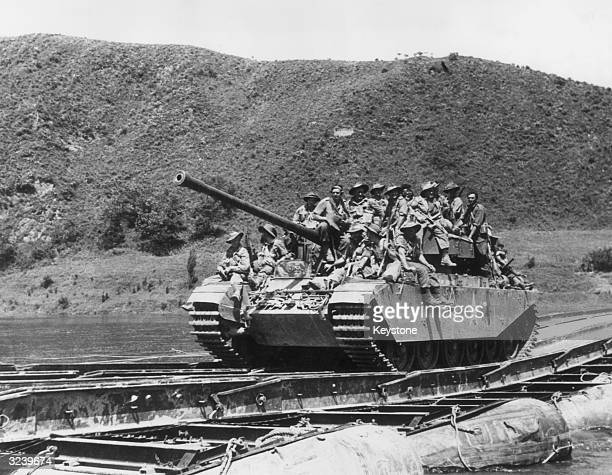Men of the 3rd Battalion Royal Australian Regiment crowded onto a Centurion tank after crossing an American-built pontoon bridge across the Injim...