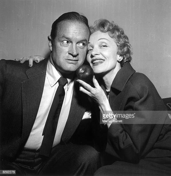 British-born comedian Bob Hope is tempted by an apple from his guest, German actor Marlene Dietrich , on the set of Hope's radio program, Hollywood,...