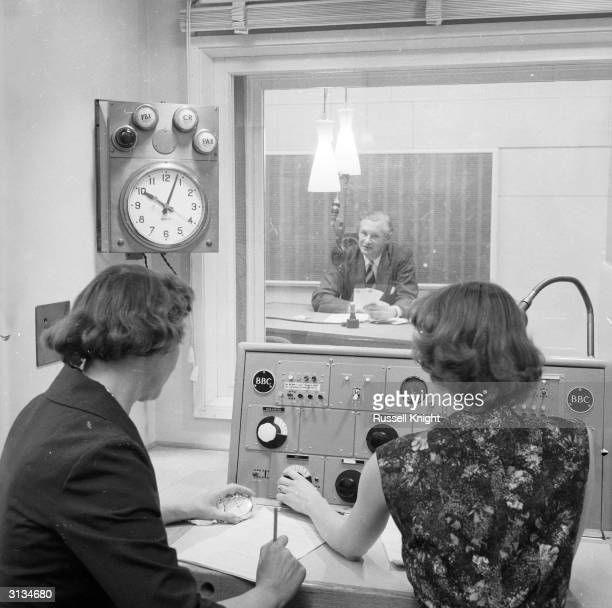 Compere Robert McDermot broadcasting an episode of 'Housewives Choice' from the BBC Record Library in London Producer Lilian Duff watches the script...