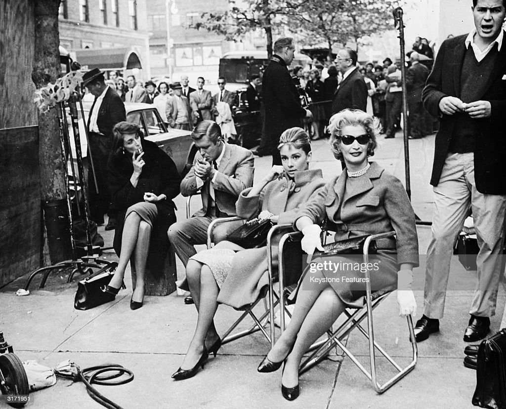 Actors take a break on a New York Street, during location filming for 'Breakfast At Tiffany's', directed by Blake Edwards. Centre left is leading man, George Peppard (1928 - 1994) and centre right is Audrey Hepburn (1929 - 1993), who plays Holly Golightly.