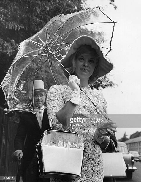 June Rifkin on Gold Cup Day at Ascot races wearing a tangerine and white lace dress and a large floppy hat and carrying a transparent umbrella