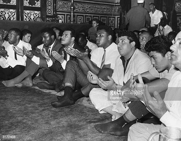 American boxer Muhammad Ali prays with his hands open in a crowd at the Hussein Mosque in Cairo Egypt He is wearing pants no shoes a shortsleeved...