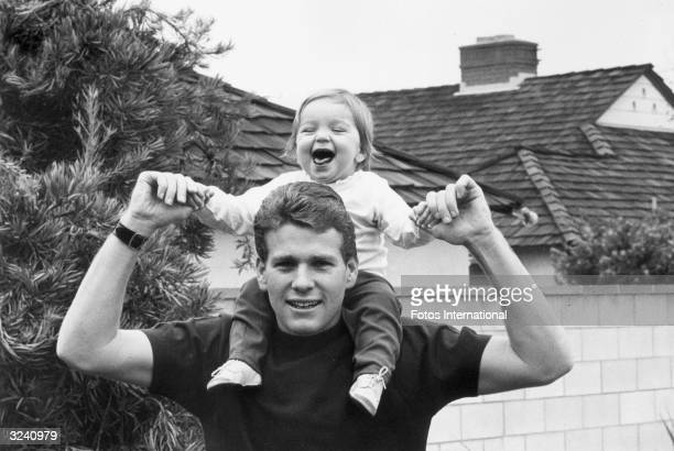 American actor Ryan O'Neal holding his smiling daughter Tatum on his shoulders in front of a house