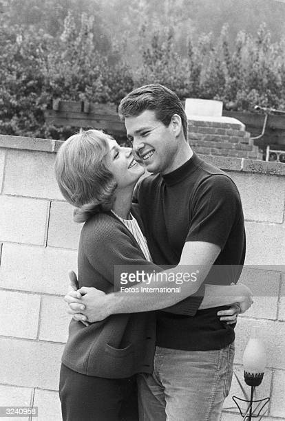 American actor Ryan O'Neal hugs his wife actor Joanna Moore outdoors in front of a stone wall Both are smiling