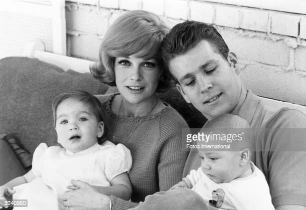 American actor Ryan O'Neal seated with his eight monthold baby son Griffin and his wife actor Joanna Moore who has their daughter Tatum on her lap
