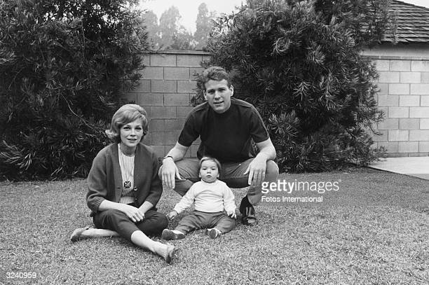 American actor Ryan O'Neal with his wife actor Joanna Moore and daughter Tatum sitting on grass in front of a stone wall