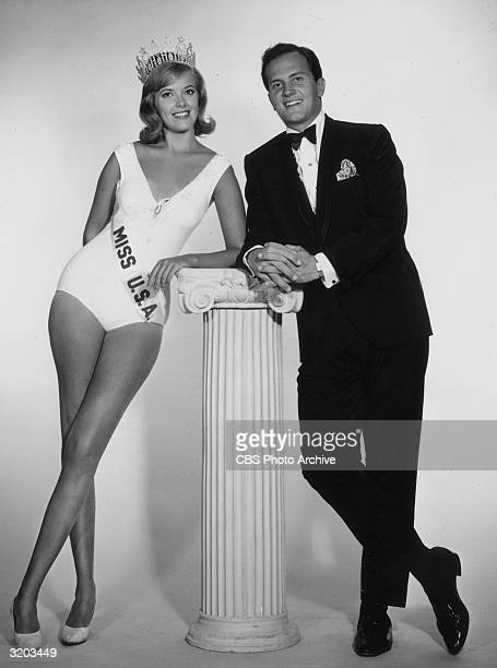 Bobbi Johnson Miss USA 1964 and American actor and singer Pat Boone lean against a pillar in a fulllength promotional portrait for the 'Miss USA 1965...