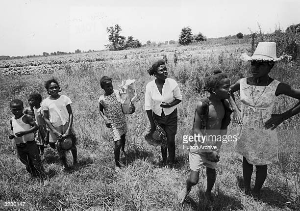AfricanAmerican children stand in the grass by a dirt road watching people marching to Jackson to encourage the AfricanAmerican vote Mississippi The...