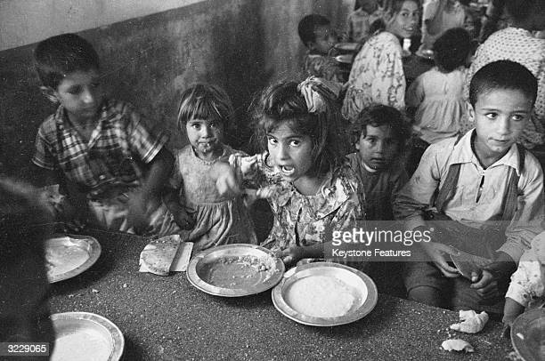 Arab children eating in the cramped quarters of one of the eight refugee camps in the Gaza Strip Free meals and medical care are supplied by the...