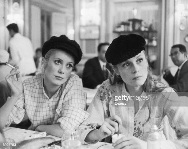 French actor Catherine Deneuve and her older sister actor Francoise Dorleac sit in a cafe in a still from director Jacques Demy's film 'Les...